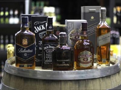 różne rodzaje whiskey i burbony stojące na beczce