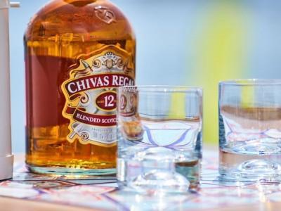 butelka whiskey Chivas Regal i dwie puste szklanki